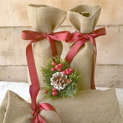 Wine bottles in burlap bags with red ribbon