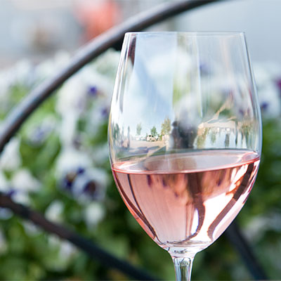 Glass of Huston Vineyards Rosé in front of spring flowers