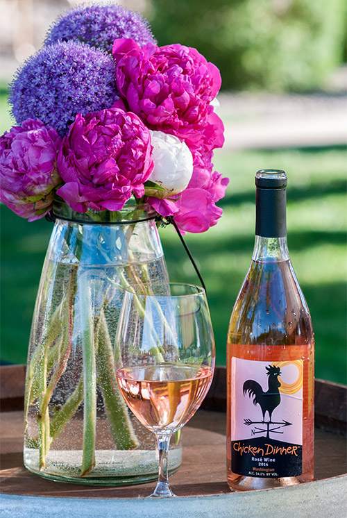 2016 Chicken Dinner Rosé bottle and glass next to bright peony flowers