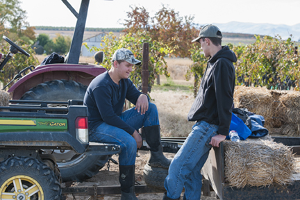 Jacob Alger and Joshua Alger sitting on tractors during the Huston Vineyards Harvest Party